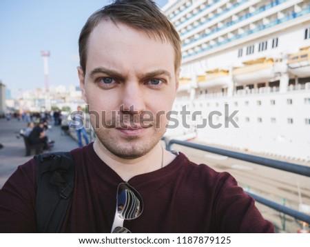 Young man makes selfie near a cruise ship.