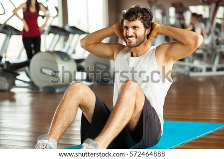 young man making abdominal exercises in gym #572464888