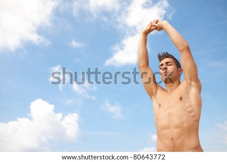 young man making elongation exercise sky background