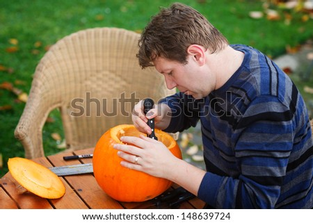 Young man making jack-o-lantern for halloween in autumn garden