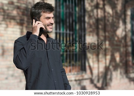Young man making phone call walking on the street . #1030928953
