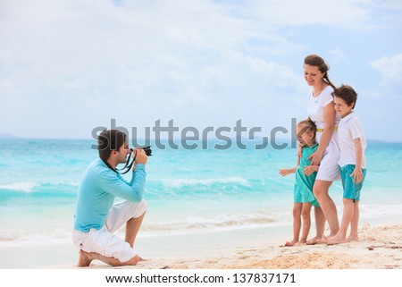 Young man making photo of his wife and kids at tropical beach
