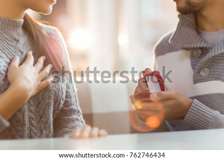 Young man making proposal to his girlfriend and giving her engagement ring