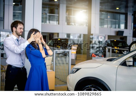 Young man making surprise to his girlfriend presenting her a new car in autosalon