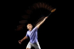 Young man, male badminton player, shuttler in motion and action on dark background. Stroboscope effect. Concept of healthy lifestyle, professional sport, action, motion, hobby, team.