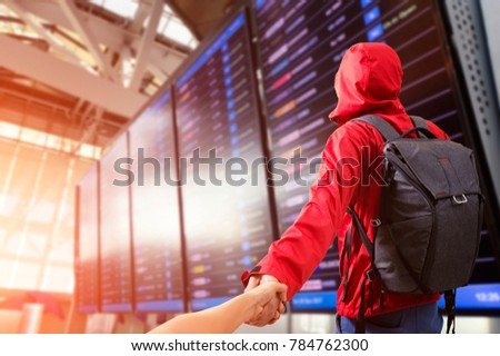 Young man Man holding hand of wife following him with backpack and carry on luggage in international airport, near flight information board.Travel Concept.