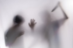 Young man Mayhem behind frosted glass.image creates feeling of fear,Behind a screen,Blurry shadow