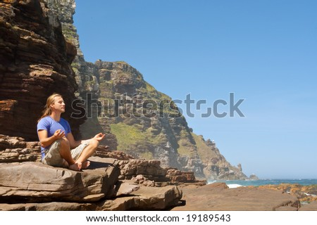 Young man meditates against sea-misty mountain background. Shot in the Cape of Good Hope and Cape Point Nature Reserve, Table Mountain National Park, near Cape Town, South Africa.