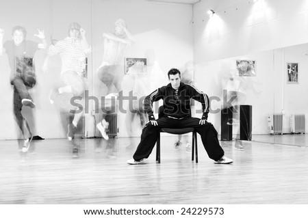 young man meditating in lotus position at dance studio