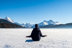 Young man meditating on the frozen Maligne Lake, in Jasper National Park, Canada