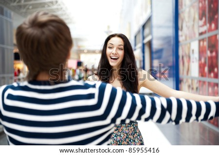 Young man meeting his girlfriend with opened arms at airport arrival hall - stock photo