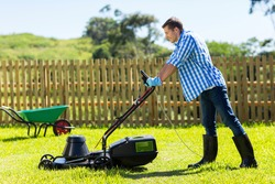 young man mowing lawn at home