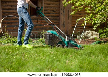 Young man mowing the lawn. Worker doing his job in backyard. Spending summer day in garden. Lawnmower standing on the background of private garden. Close up. #1405884095