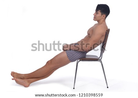 Young man naked and relaxed  sitting on a chair