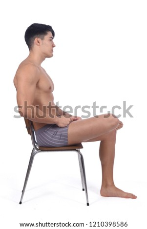 Young man naked and sitting on a chair