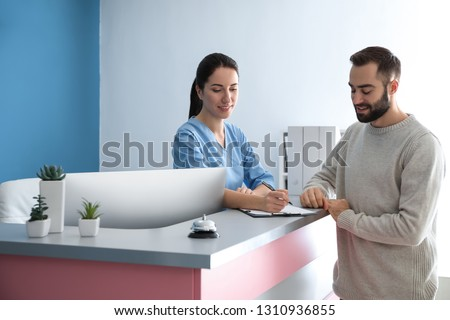 Young man near reception desk in clinic Photo stock ©