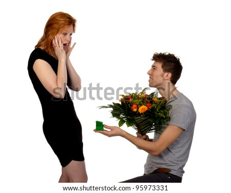 Young man offers his surprised girlfriend a large bouquet of flowers and a ring, isolated on a white background