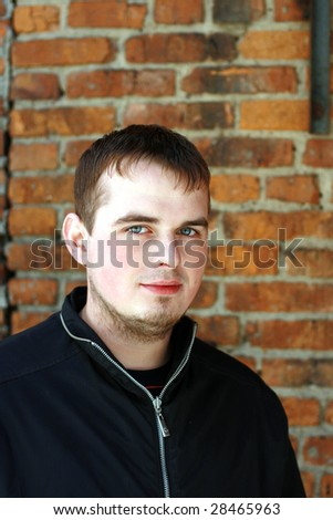 Young man on a brick wall