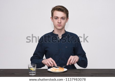 young man on a white background is sitting at a table and eating food from a plate. He sits right in front of the camera smiling and looking happy #1137983078