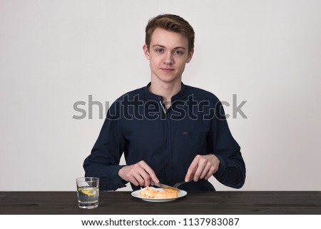 young man on a white background is sitting at a table and eating food from a plate. He sits right in front of the camera smiling and looking happy #1137983087