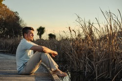 Young man on bare feet sitting on wooden walkway on lake shore during sunset. Inspirational concept