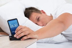 Young Man On Bed Snoozing Alarm Clock On Cell Phone Screen