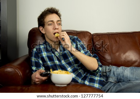 Young Man On Couch Eating Potato Chips Stock Photo