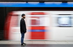 Young man on his side with a mask on the subway platform. The movement of the subway caravan in the background. The train passing quickly. Copy space.
