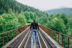 Young man on railway track on forest background. The observation deck.