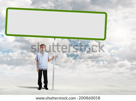 Young man on road holding blank banner. Place for text