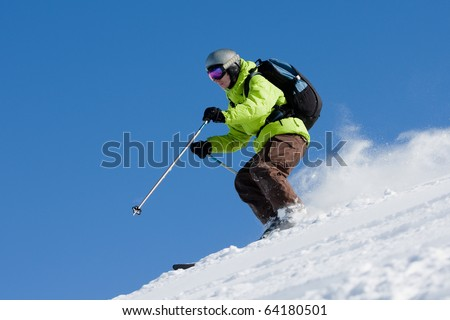Young man on skis out of slopes. Off-piste skiing - stock photo