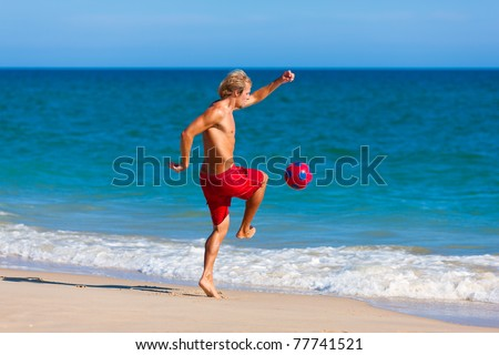 Young man on the beach playing soccer in his vacation