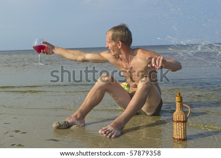 Young man on the beach with wine.