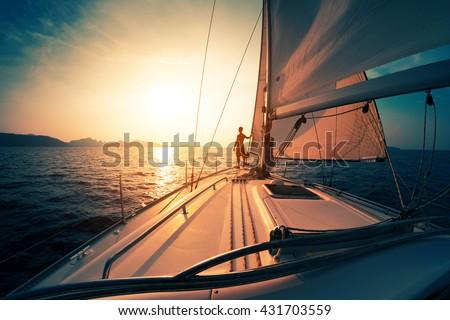 Young man on the sailing boat at sunset