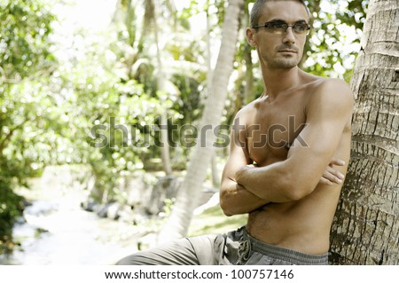 Young man on vacations leaning on a palm tree trunk and wearing sunglasses.
