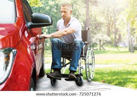 Young Man On Wheelchair Opening Red Car Door In The Park #725071276