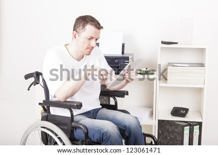 Young man on wheelchair working in a Office, using a tablet computer