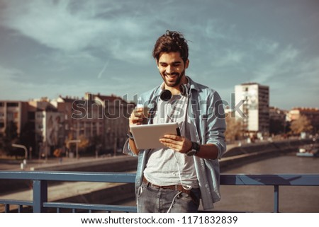 Young man online via a digital tablet in the city
