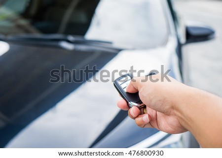 Young man opening his car door with the control remote key. #476800930
