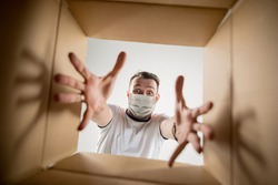 Young man opening the huge postal package wearing protective face mask. Male model on top of cardboard box. Food and goods contactless delivery during coronavirus quarantine for isolated people.