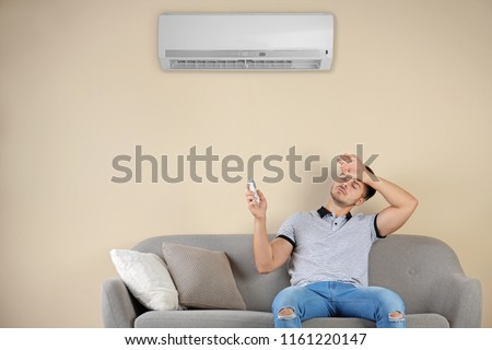 Young man operating air conditioner while sitting on sofa at home #1161220147