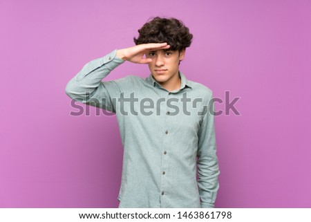 Young man over isolated purple wall looking far away with hand to look something