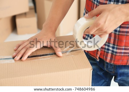 Young man packing box, indoors