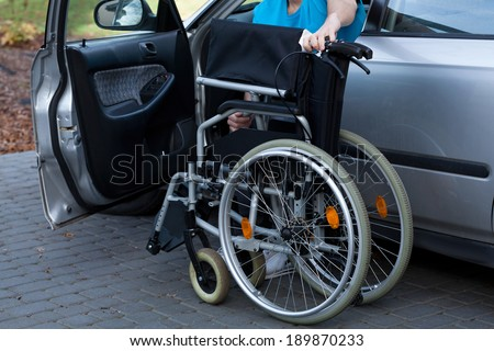 Young man packing wheelchair into a car at parking #189870233