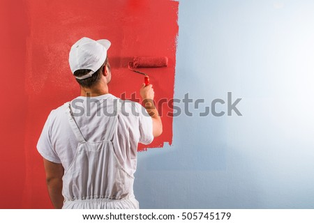 Shutterstock Young man painting wall with roller
