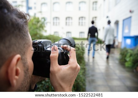 Young Man Paparazzi Photographer Capturing A Photo Suspiciously Of Couple Walking Together Using A Camera Foto d'archivio ©
