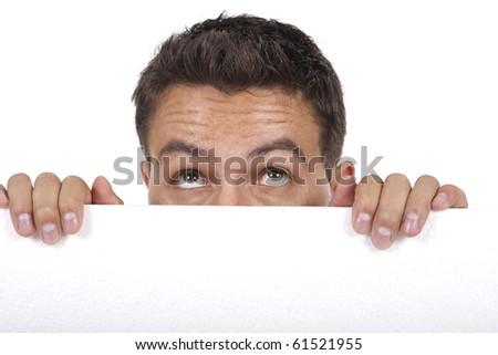 young man peeking behind empty white billboard