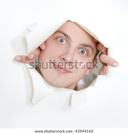 young man peeping through hole in paper