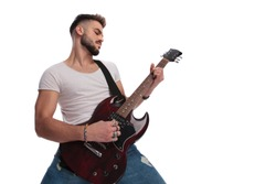 young man performing a rock and roll concert on electric guitar while standing on white background
