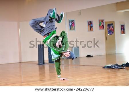 young man performing break dance in dance studio